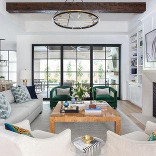 Cette image montre un très grand salon traditionnel ouvert avec un mur blanc, un sol en bois clair, une cheminée standard, un manteau de cheminée en pierre, un téléviseur fixé au mur, un plafond en poutres apparentes et du lambris.
