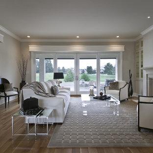 Modernes Wohnzimmer mit beiger Wandfarbe, braunem Holzboden, Kamin und Kaminsims aus Stein in Austin