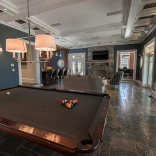 Esempio di un ampio soggiorno tradizionale stile loft con pareti blu, pavimento in pietra calcarea, cornice del camino in pietra e TV a parete