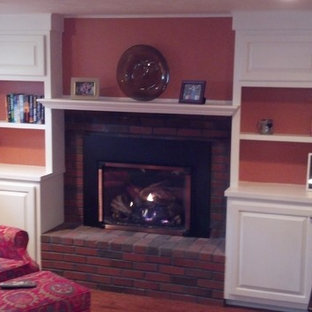 Photo of a mid-sized traditional formal enclosed living room in Boston with orange walls, dark hardwood floors, a standard fireplace, a brick fireplace surround, no tv and brown floor.