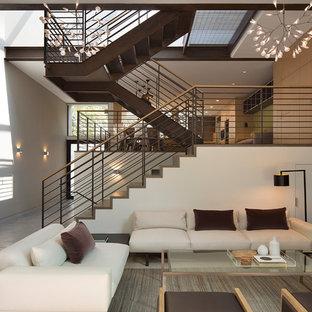 Immagine di un piccolo soggiorno minimalista stile loft con angolo bar, pareti bianche, pavimento in cemento, camino classico, cornice del camino in metallo e TV a parete