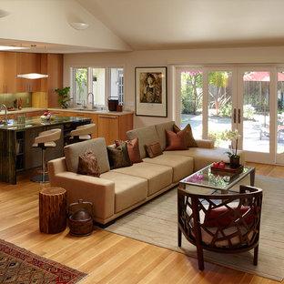 Foto de salón abierto, actual, de tamaño medio, sin chimenea, con suelo naranja, paredes beige, suelo de madera clara y televisor colgado en la pared