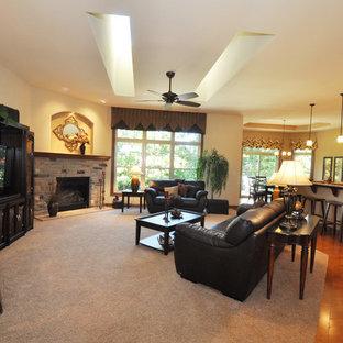 Modelo de salón abierto, clásico, grande, con paredes beige, moqueta, chimenea de esquina, marco de chimenea de piedra y televisor independiente