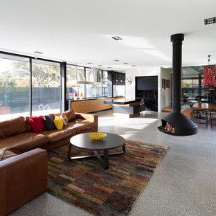 Foto de salón abierto, actual, grande, con chimeneas suspendidas, paredes blancas y suelo de cemento