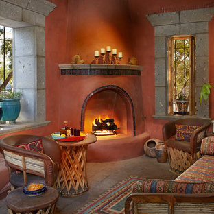 他の地域のサンタフェスタイルのおしゃれなリビング (オレンジの壁、コーナー設置型暖炉、タイルの暖炉まわり、茶色い床) の写真