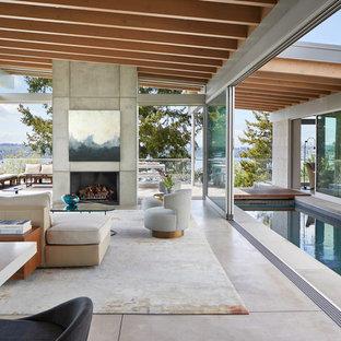 Modelo de salón para visitas abierto, contemporáneo, extra grande, con paredes grises, suelo de cemento, chimenea tradicional, marco de chimenea de hormigón, televisor retractable y suelo gris