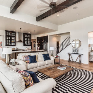 Example of a country open concept light wood floor living room design in Boise with white walls