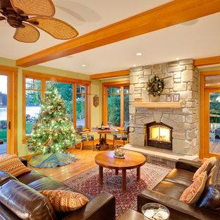 Modelo de salón abierto, clásico, con paredes verdes, suelo de madera clara, marco de chimenea de piedra y suelo naranja