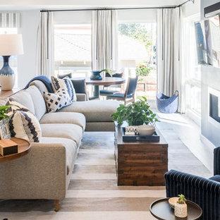 Idéer för ett mellanstort 50 tals allrum med öppen planlösning, med en hemmabar, blå väggar, mellanmörkt trägolv, en bred öppen spis, en spiselkrans i metall och en väggmonterad TV