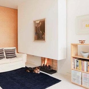 Ispirazione per un soggiorno nordico di medie dimensioni e aperto con libreria, pareti bianche, nessuna TV, pavimento in cemento, camino sospeso, cornice del camino in mattoni e pavimento bianco