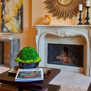Exemple d'un salon chic avec un mur orange et un manteau de cheminée en pierre.