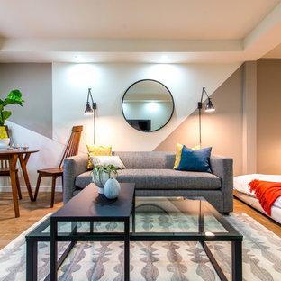 Foto de salón abierto, minimalista, de tamaño medio, sin chimenea, con televisor independiente, paredes multicolor y suelo de madera clara