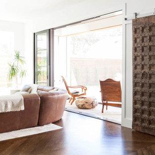 Modern inredning av ett litet allrum med öppen planlösning, med ett finrum, vita väggar, mellanmörkt trägolv, en standard öppen spis, en spiselkrans i sten och en väggmonterad TV