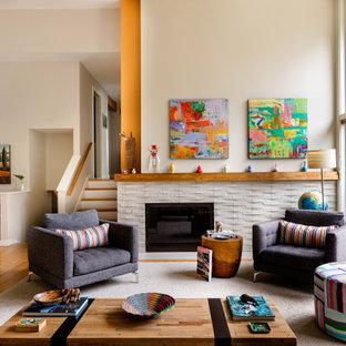 Esempio di un soggiorno design di medie dimensioni e aperto con pavimento in legno massello medio, camino classico, cornice del camino in pietra, nessuna TV, pareti beige e pavimento marrone