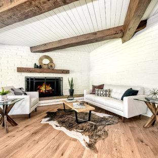 Großes, Offenes Mid-Century Wohnzimmer mit weißer Wandfarbe, hellem Holzboden, Kamin, Kaminsims aus Backstein und braunem Boden in San Diego