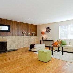 Offenes Retro Wohnzimmer mit beiger Wandfarbe, hellem Holzboden, Kamin und Kaminumrandung aus Backstein in San Francisco