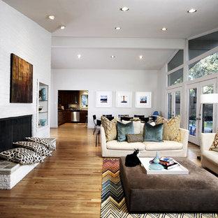 Ejemplo de salón abierto, vintage, grande, sin televisor, con paredes blancas, suelo de madera en tonos medios, chimenea de doble cara, marco de chimenea de ladrillo y suelo marrón