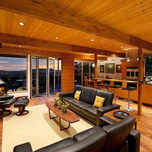 Cette image montre un grand salon vintage ouvert avec un mur beige, un sol en bois brun, cheminée suspendue, un manteau de cheminée en métal, un téléviseur fixé au mur et un sol marron.