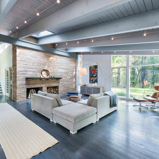 Large midcentury formal open concept living room in Boston with white walls, dark hardwood floors, a standard fireplace, a stone fireplace surround, no tv and grey floor.