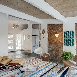 Mittelgroßes, Offenes Mid-Century Wohnzimmer ohne Kamin mit weißer Wandfarbe, Schieferboden, Wand-TV und grauem Boden in Grand Rapids