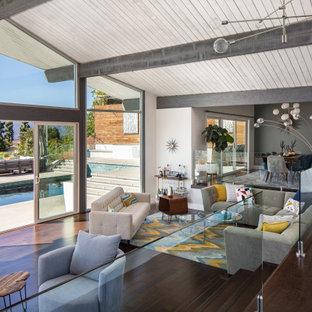ロサンゼルスの広いミッドセンチュリースタイルのおしゃれなリビング (白い壁、濃色無垢フローリング、コーナー設置型暖炉、石材の暖炉まわり、テレビなし、茶色い床、三角天井) の写真