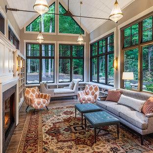 Foto på ett mycket stort 50 tals allrum med öppen planlösning, med ett bibliotek, grå väggar, mörkt trägolv, brunt golv, en standard öppen spis, en spiselkrans i trä och en dold TV