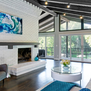 Example of a mid-sized mid-century modern open concept dark wood floor and brown floor living room design in Columbus with white walls, a brick fireplace and a standard fireplace