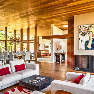 Inspiration for a large contemporary formal and open concept medium tone wood floor living room remodel in Santa Barbara with a standard fireplace and a brick fireplace