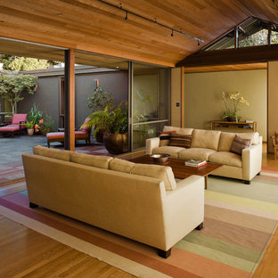 Example of a large minimalist open concept medium tone wood floor living room design in San Francisco with beige walls