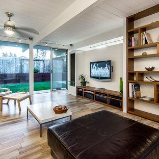 Ejemplo de biblioteca en casa abierta, moderna, de tamaño medio, con paredes blancas, televisor colgado en la pared, suelo de baldosas de porcelana y suelo beige