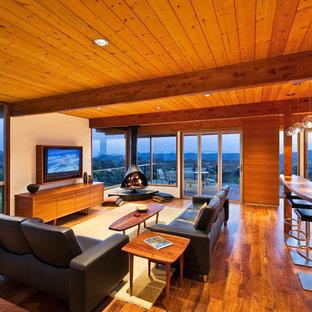 Inspiration för ett 60 tals allrum med öppen planlösning, med ett finrum, mellanmörkt trägolv, en väggmonterad TV och en hängande öppen spis