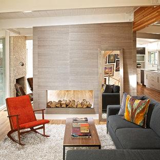 Modelo de salón abierto, minimalista, de tamaño medio, con paredes grises, suelo de madera en tonos medios y chimenea de doble cara