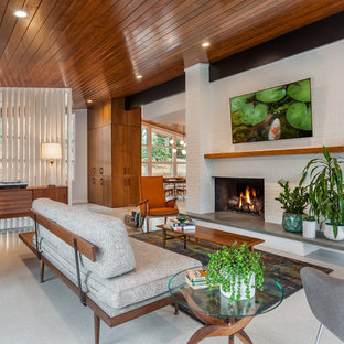 Inredning av ett retro separat vardagsrum, med vita väggar, en standard öppen spis, en spiselkrans i tegelsten, en väggmonterad TV och grått golv