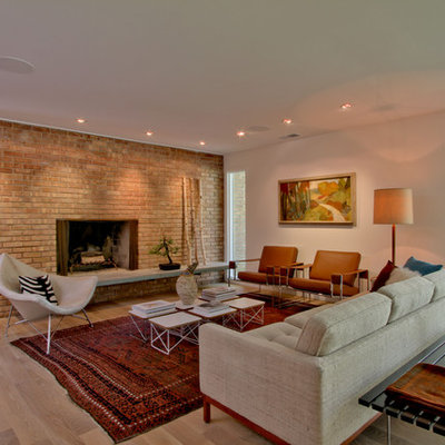 Inspiration for a mid-sized 1950s open concept and formal light wood floor and beige floor living room remodel in Indianapolis with white walls, a standard fireplace, a brick fireplace and no tv