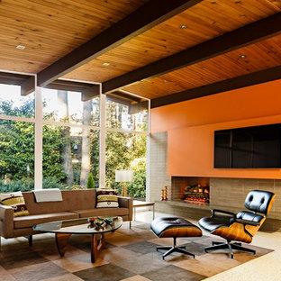 Aménagement d'un salon rétro de taille moyenne et ouvert avec un mur orange, un téléviseur fixé au mur, une cheminée standard et un manteau de cheminée en brique.