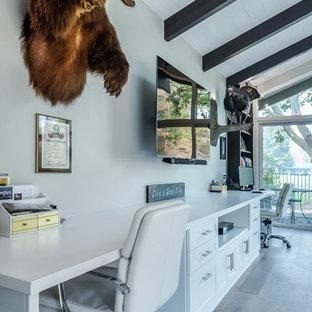 Immagine di un grande soggiorno minimalista chiuso con angolo bar, pareti grigie, pavimento in legno massello medio, nessun camino, TV a parete e pavimento marrone
