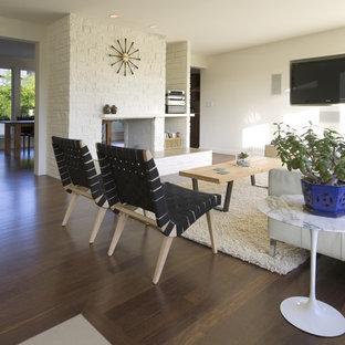 Immagine di un soggiorno minimalista con pavimento marrone, pareti bianche, cornice del camino in mattoni e TV a parete
