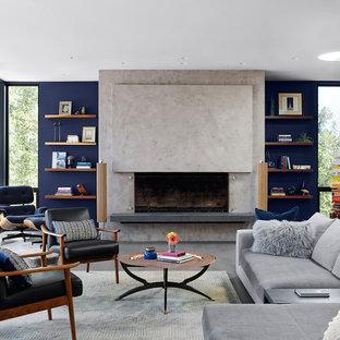 Inredning av ett 60 tals allrum med öppen planlösning, med blå väggar, en standard öppen spis och grått golv