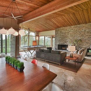 Modelo de salón abierto, vintage, con chimenea tradicional y marco de chimenea de piedra