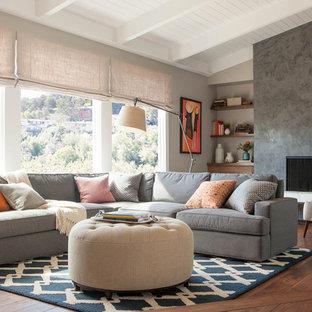 Diseño de salón actual, grande, con suelo de madera oscura, marco de chimenea de yeso, paredes grises, pared multimedia y chimenea lineal