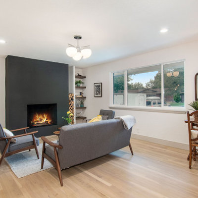 Living room - mid-sized 1950s open concept light wood floor and beige floor living room idea in Denver with white walls, a standard fireplace, a plaster fireplace and no tv