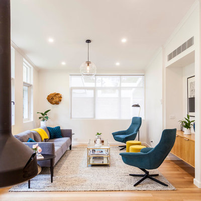 Mid-sized 1960s open concept medium tone wood floor and brown floor living room photo in Melbourne with white walls, a hanging fireplace and no tv