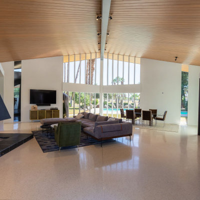 Large 1960s open concept white floor and vaulted ceiling living room photo in Other with a bar, white walls, a standard fireplace, a metal fireplace and a wall-mounted tv