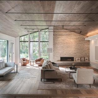 Idée de décoration pour un salon vintage ouvert avec un mur blanc, un sol en bois brun, une cheminée ribbon, un manteau de cheminée en pierre de parement, un téléviseur fixé au mur, un sol marron, un plafond voûté et un plafond en bois.