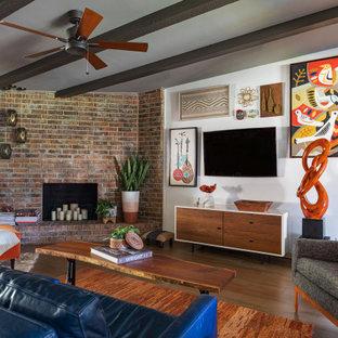 Offenes Mid-Century Wohnzimmer mit weißer Wandfarbe, braunem Holzboden, Kamin, Kaminumrandung aus Backstein, Wand-TV, braunem Boden, freigelegten Dachbalken und Ziegelwänden in Houston