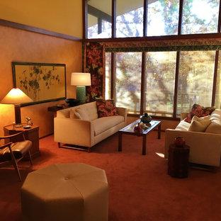 Cette photo montre un salon rétro de taille moyenne et fermé avec un mur orange, moquette, une cheminée standard, un manteau de cheminée en brique, aucun téléviseur et un sol orange.