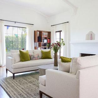 Ejemplo de salón para visitas moderno con paredes blancas, suelo de madera en tonos medios, chimenea tradicional y suelo marrón