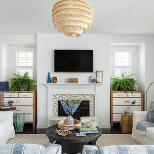 ローリーの中サイズのビーチスタイルのおしゃれなLDK (白い壁、濃色無垢フローリング、タイルの暖炉まわり、壁掛け型テレビ、茶色い床、標準型暖炉) の写真