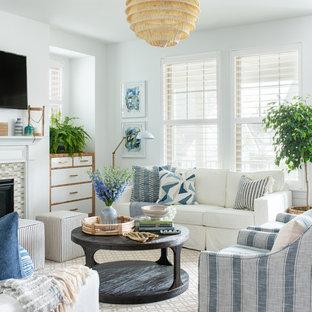 ローリーの中サイズのビーチスタイルのおしゃれなLDK (白い壁、濃色無垢フローリング、タイルの暖炉まわり、壁掛け型テレビ、茶色い床) の写真