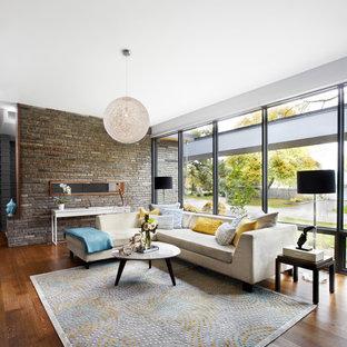 Immagine di un soggiorno moderno con sala formale e pavimento in legno massello medio